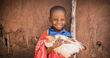 Mlonra, age 7, with a chicken in Mashuru ADP.