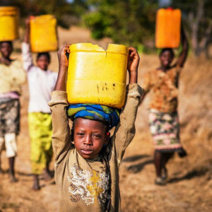 Dorcas Hamasamu, 9, (red skirt) carries a leaking bucket of water back from the Bulanda water hole water hole.